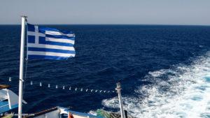 Greek flag waving in wind at back of boat
