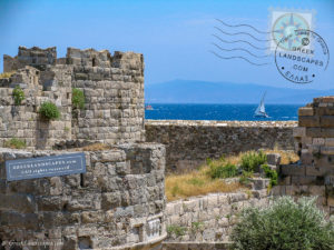 Stone walls of Neratzia medieval fort with boats in the sea beyond