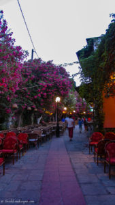Night view of Kos town cafes under blooming flowers