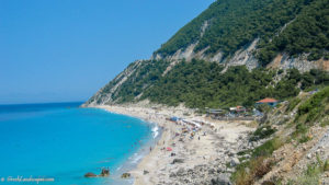 Busy beach in front of mountain