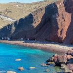 Red cliff above beach, and blue sea water