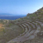 Makyneia theatre. Stone seating and orchestra with the sea beyond.